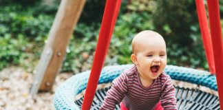 A nine month-old baby playing on the swing