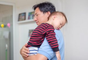 A 2-year-old sleeping on his dad's shoulders