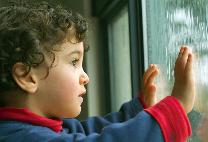A child watching the rain through the window