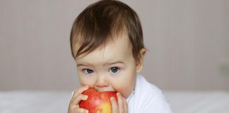 A baby holding an apple.