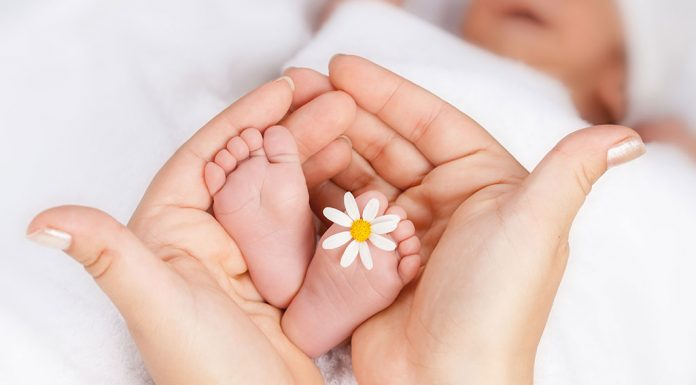 A mother holding her baby's feet with a flower on it