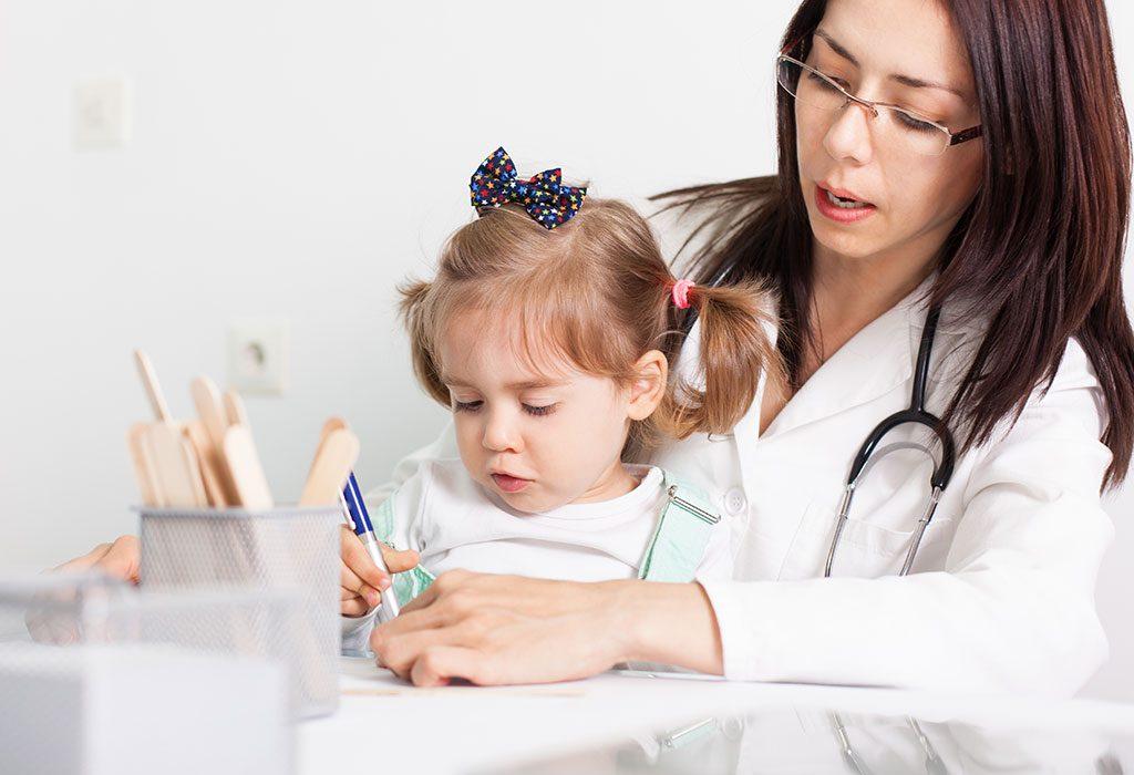 A doctor examining a little girl