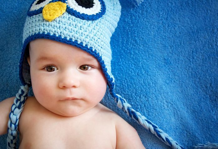 A 16 week-old baby wearing an owl hat