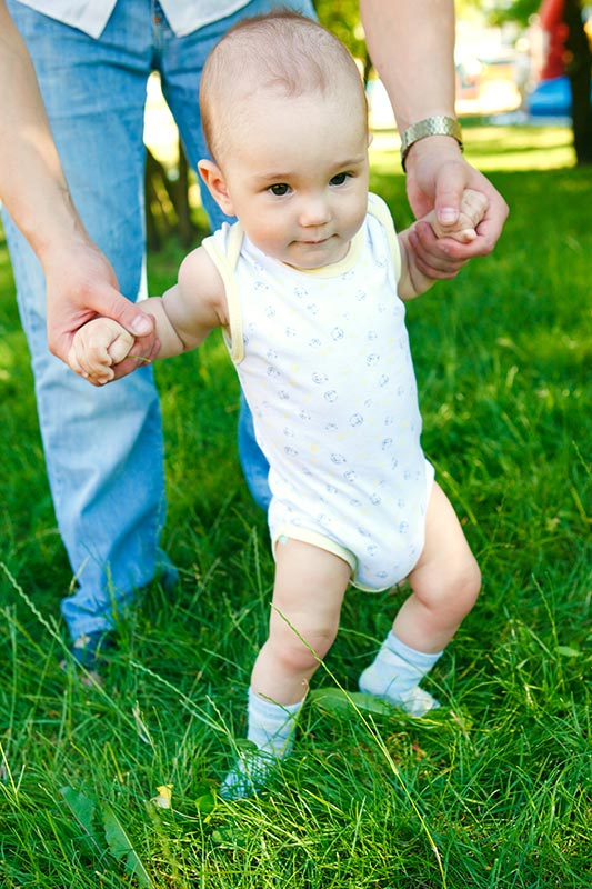 A baby trying to walk.