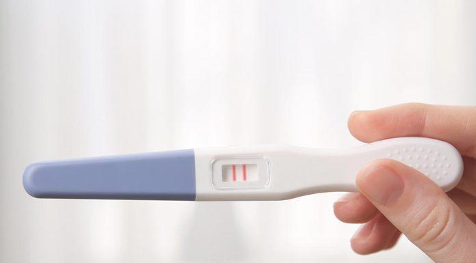A woman holding a positive pregnancy test kit