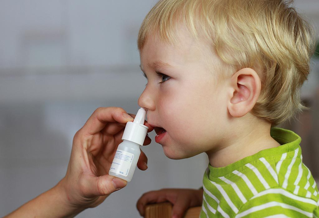 Mother administering nasal spray to baby