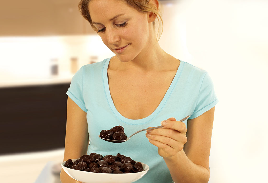 A woman eating prunes