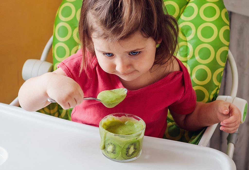 Toddler eating mashed kiwi