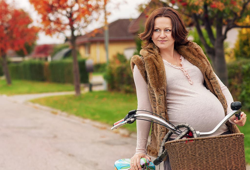 A pregnant woman standing with a bicycle