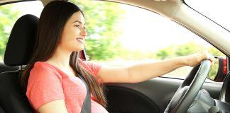 A pregnant woman driving a car