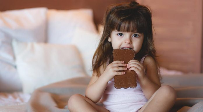 A little girl eating a chocolate