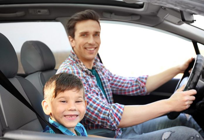 A child sitting in the front seat of a car with his father