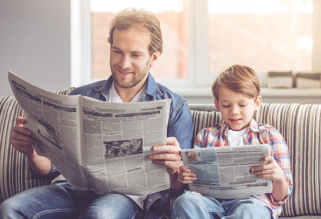 Child and father reading newspaper