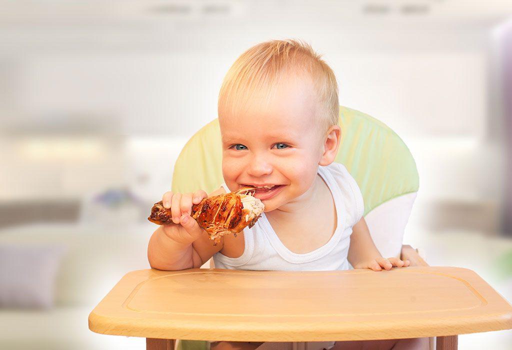 Toddler eating chicken