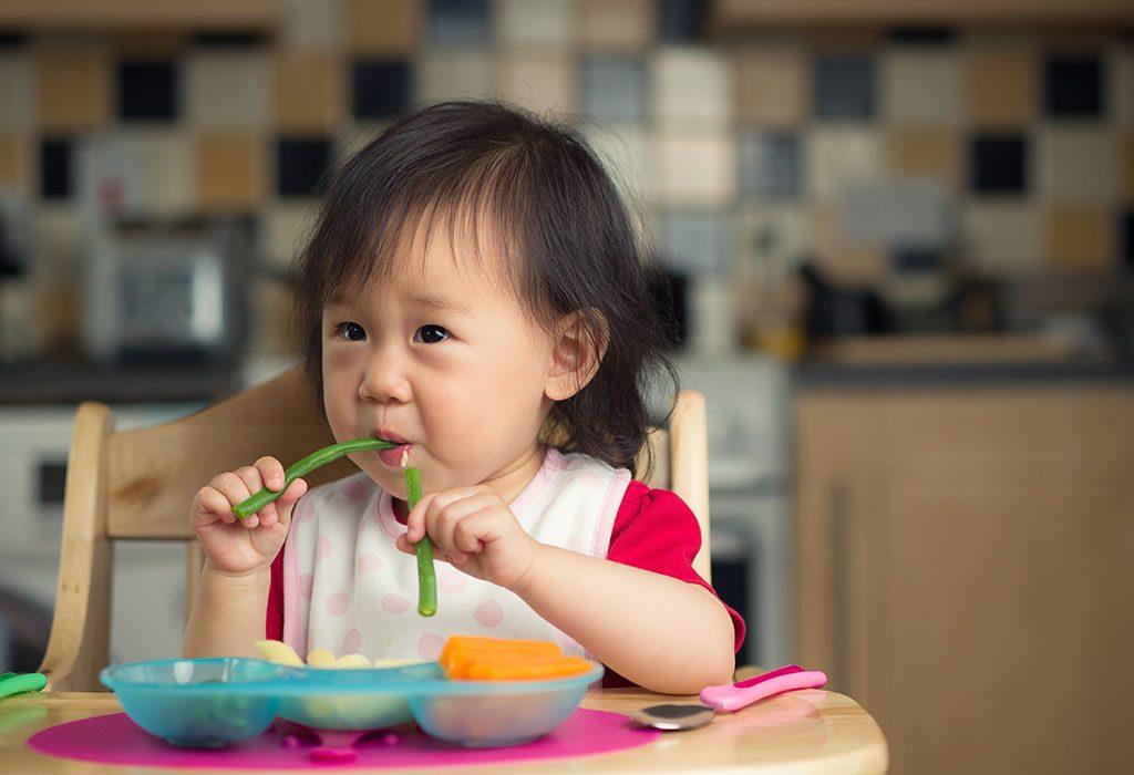 Toddler eating beans