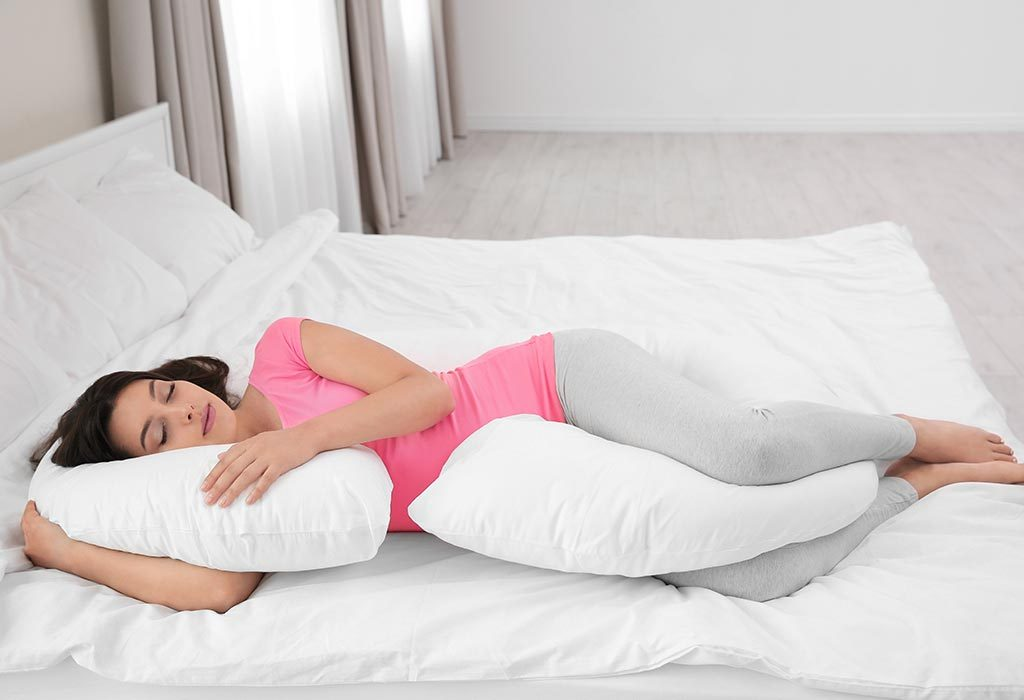 Woman sleeps with a pillow between her knees