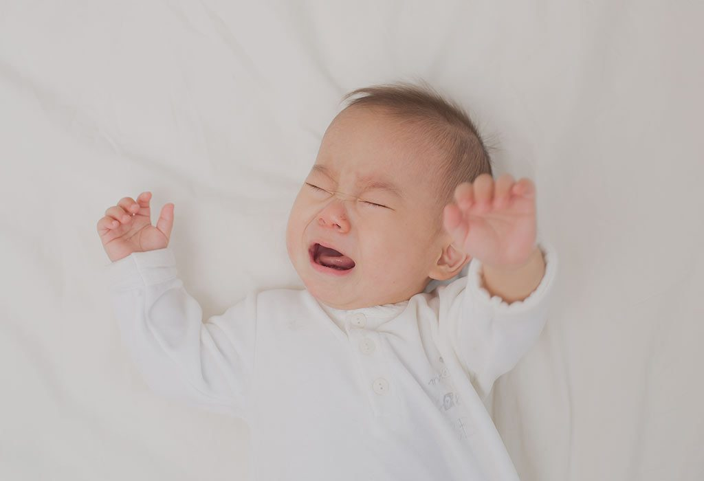 A baby crying on being put down on the bed