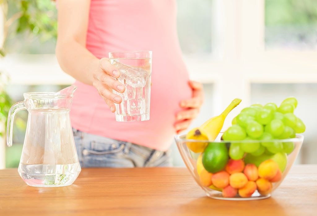 A pregnant woman with a glass of water in her hand