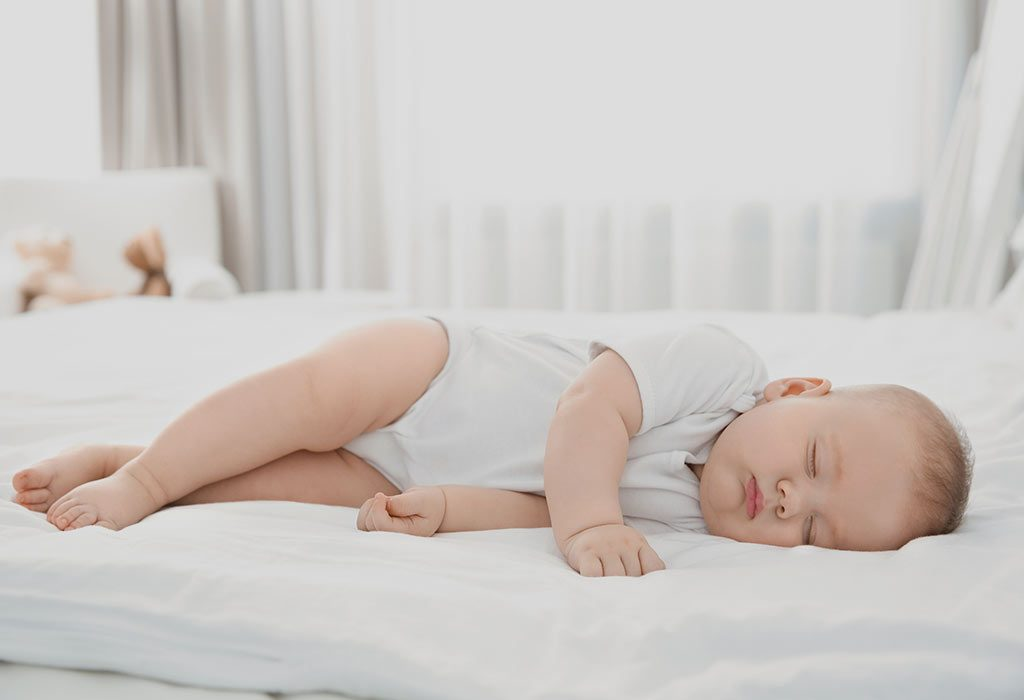 A baby sleeping in a room with a ceiling fan