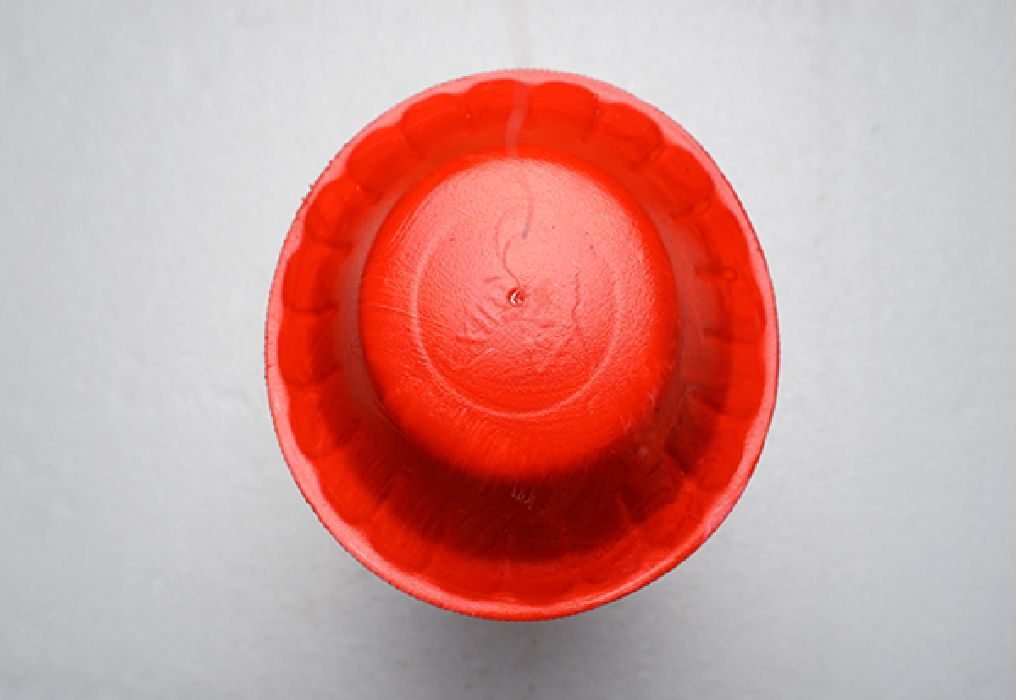 Now, cut some string to about a length of 6 inches and insert it through the hole you made in your paper bowl in Step 1.