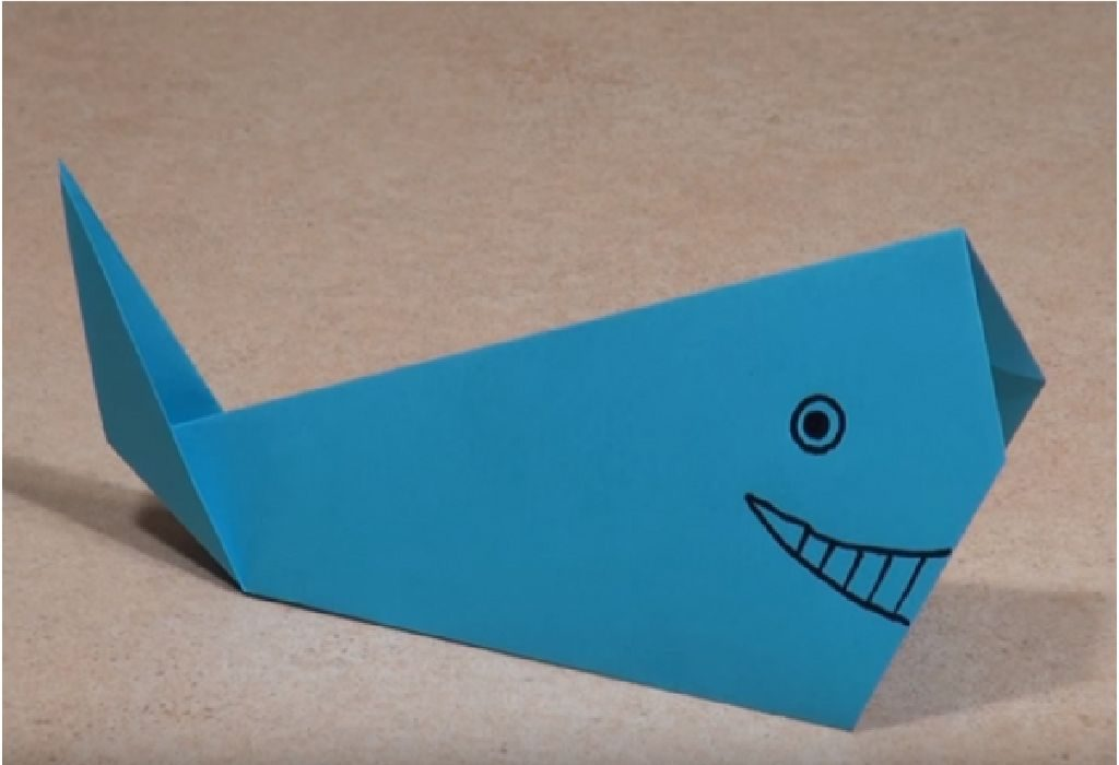 Using a marker and make the eyes and the mouth of the whale.