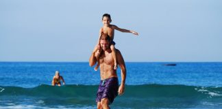 Father lifting Son while riding Surfboard