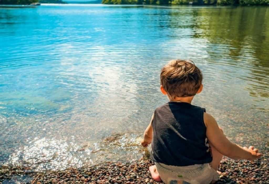 Child seating along lake side