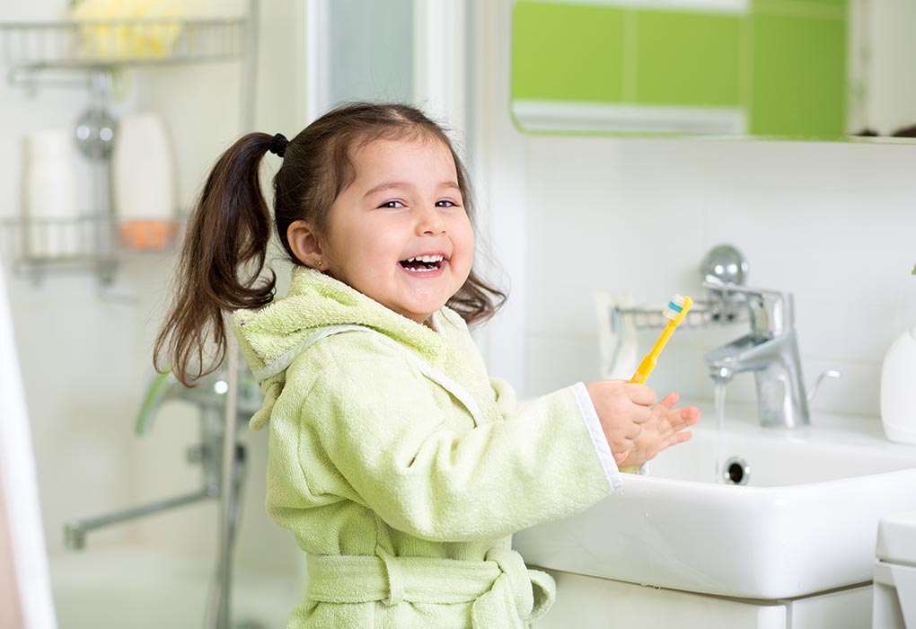 Girl brushing her own teeth