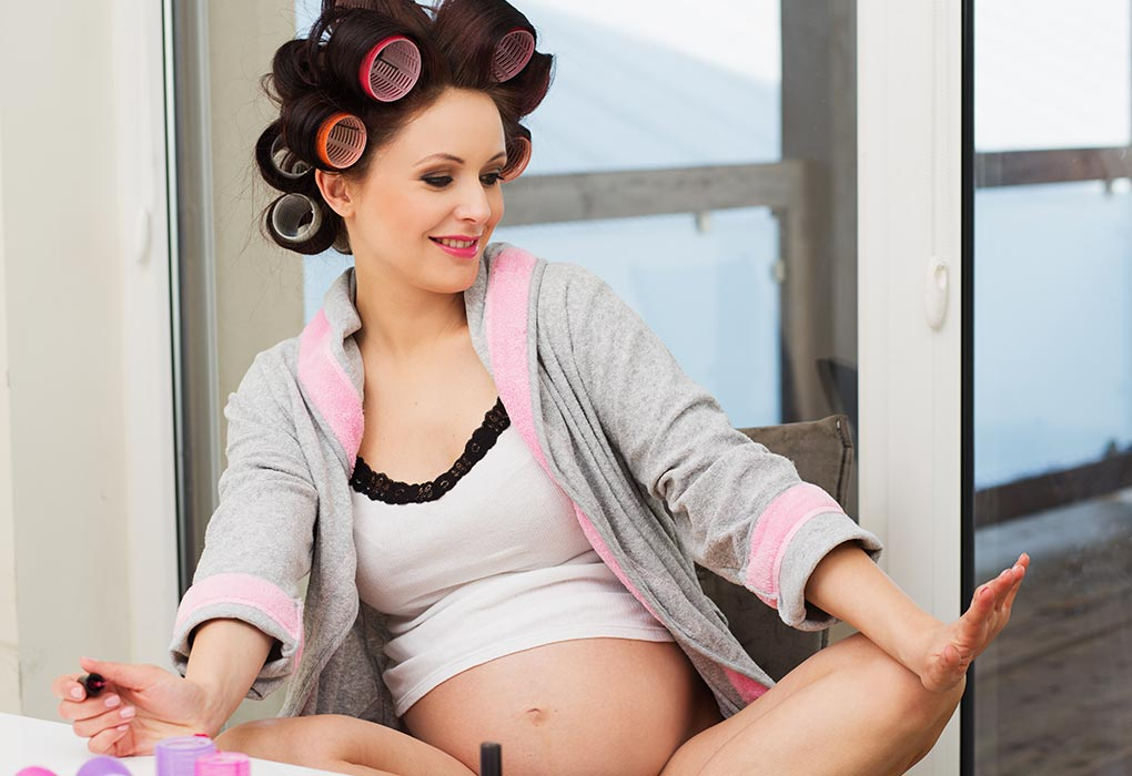 A pregnant woman with rollers in her hair