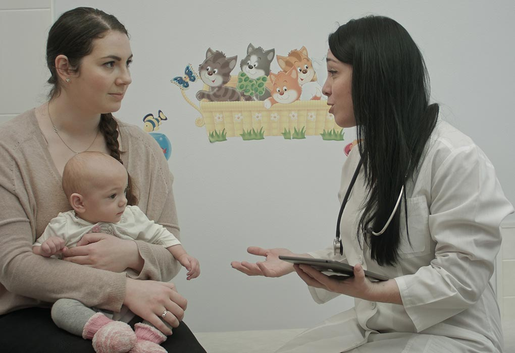 A woman with her baby talking to a doctor
