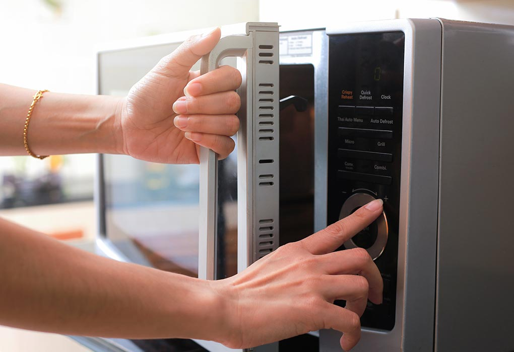 A woman using a microwave