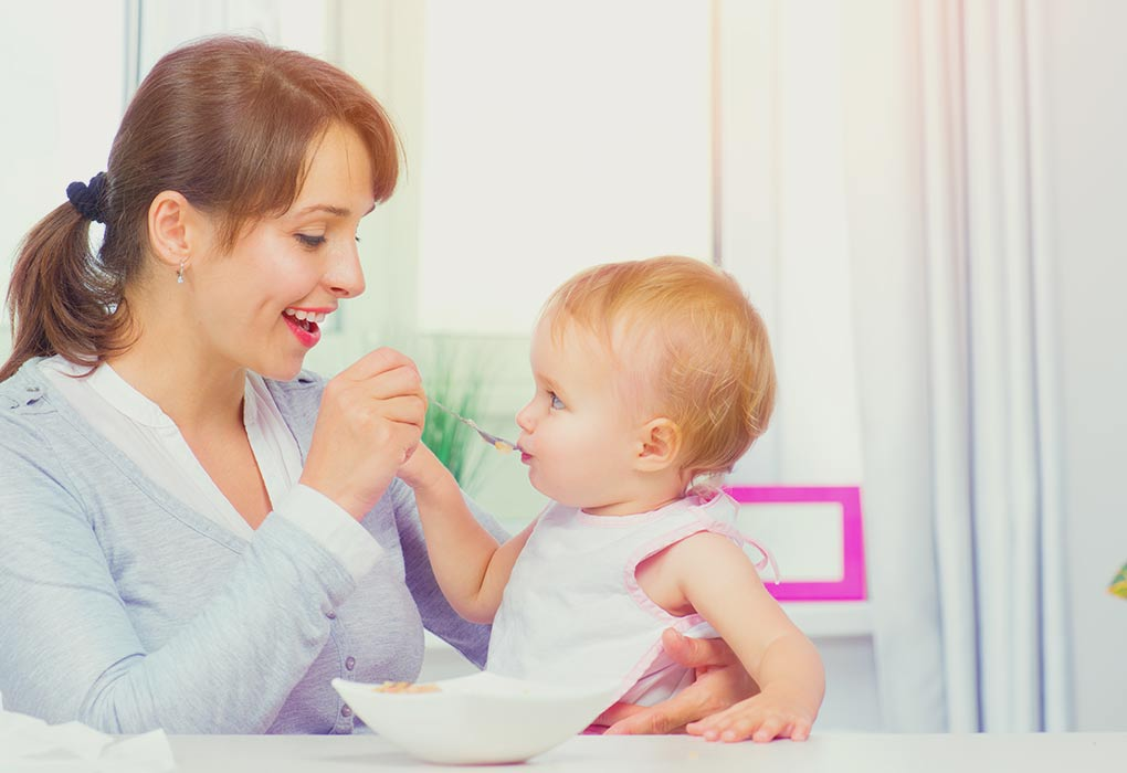 A mother gives solid food to her baby
