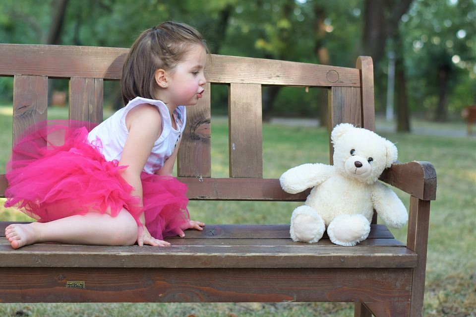 girl talking to teddy
