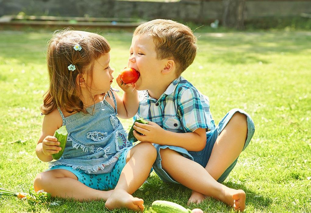 Siblings eating veggies together