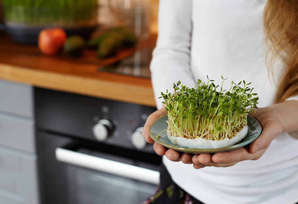 Woman holding alfalfa in kitchen