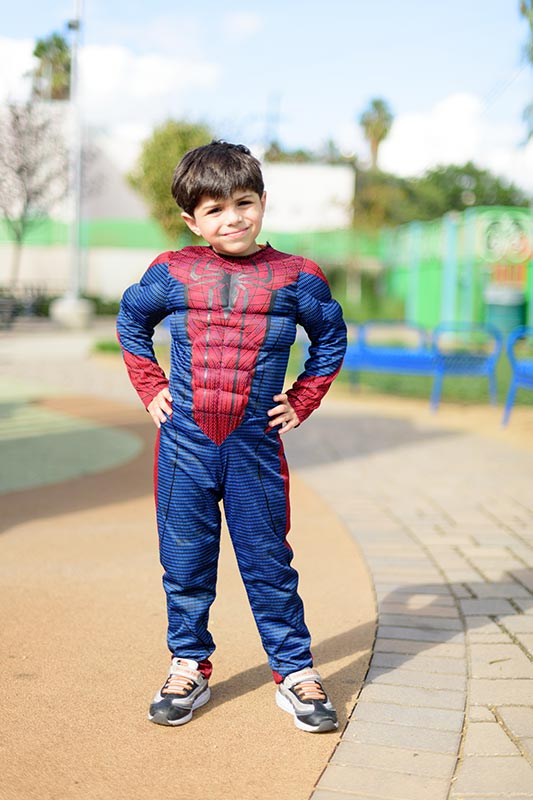 A kid wearing spiderman costume