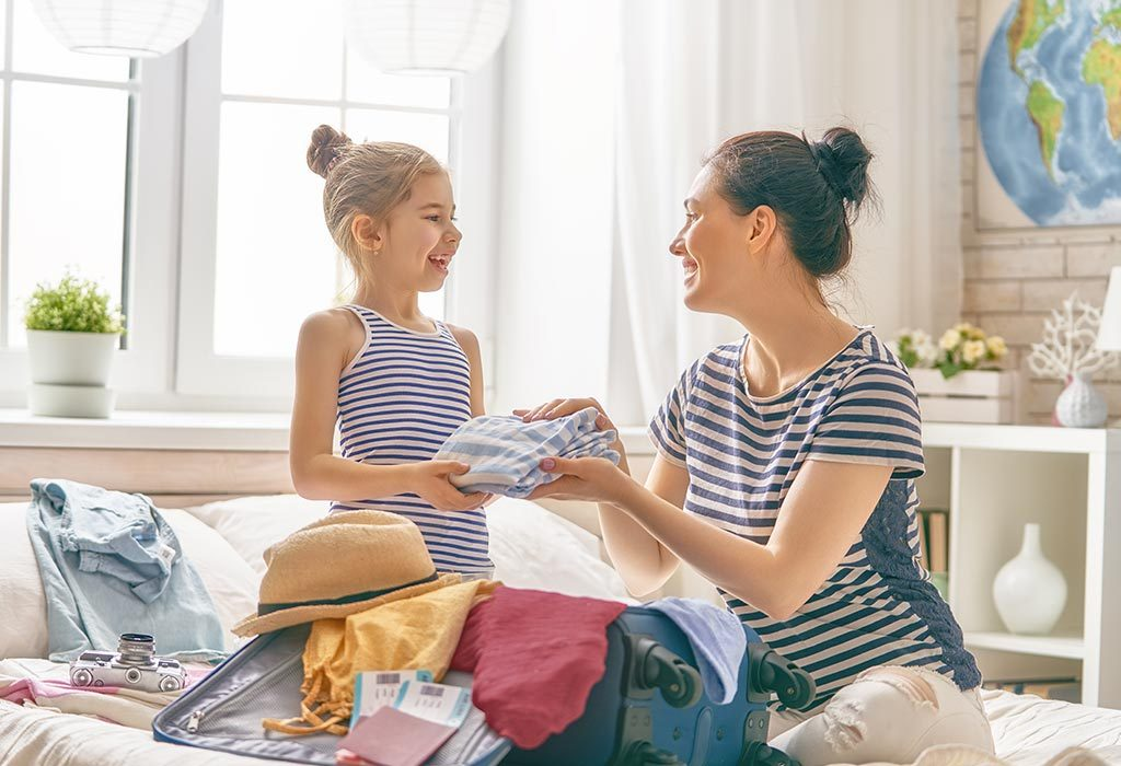 Single mom and daughter packing a suitcase for vacation