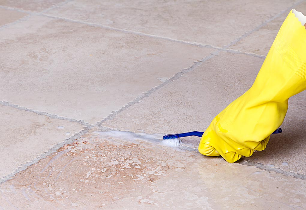 A woman cleaning bathroom grout