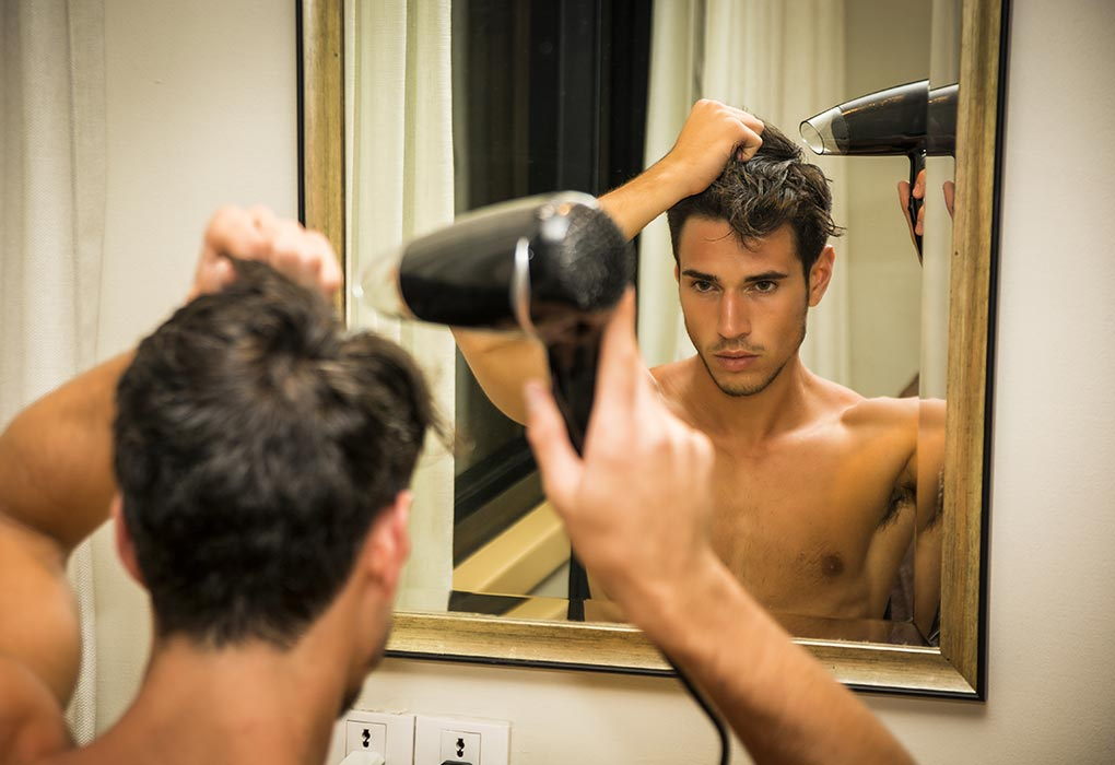 Attractive man drying his hair
