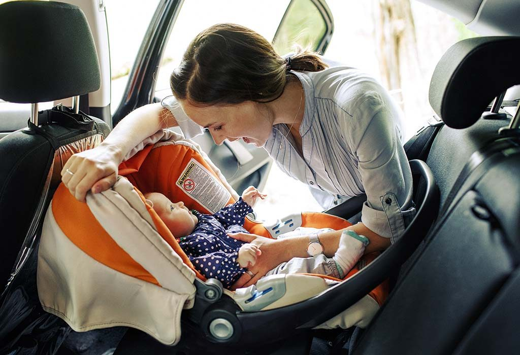 A woman looking at her baby sitting in a baby car seat