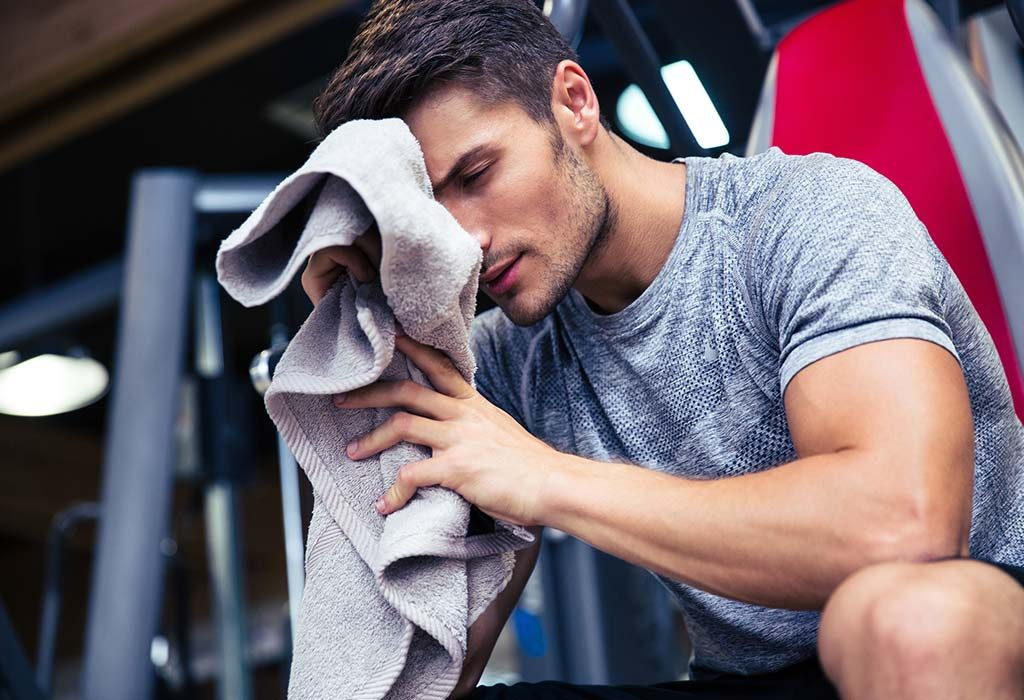 A man wiping his face with a towel
