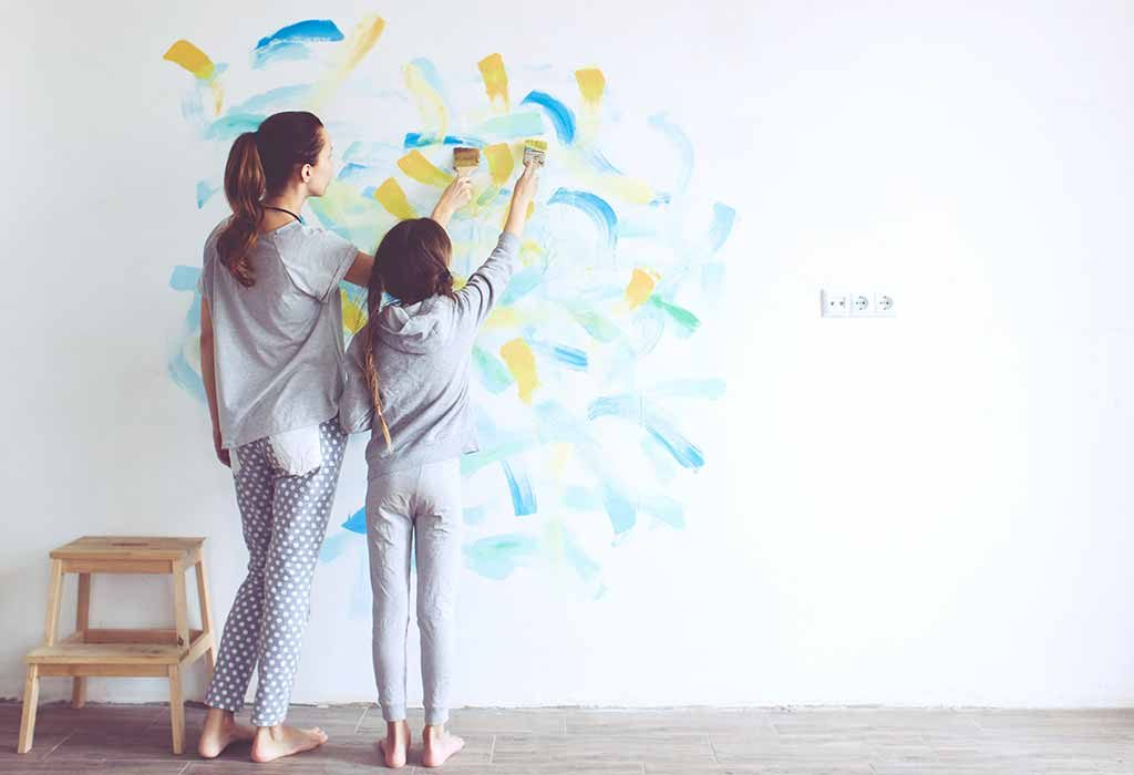 Mother and daughter painting a wall of the house