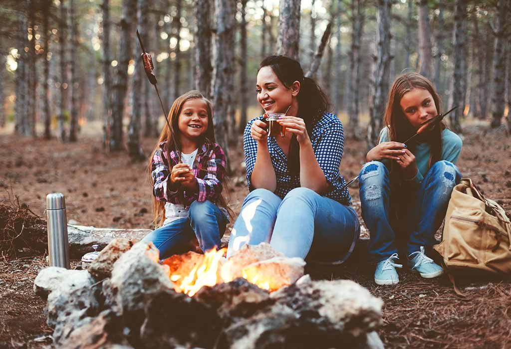 Mother and daughters enjoying a campfire