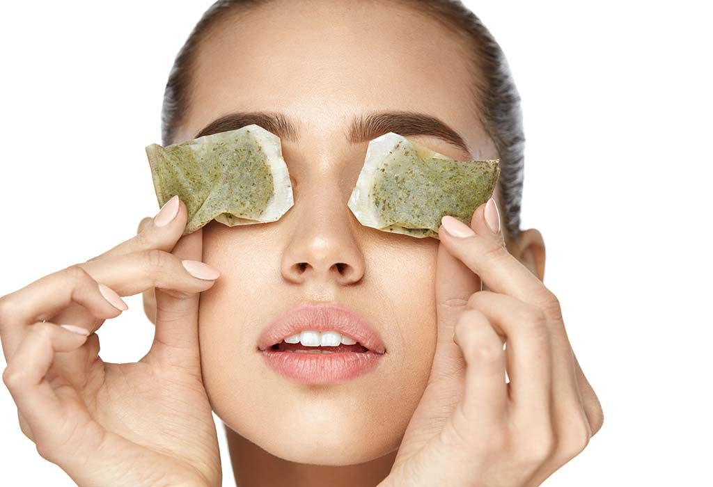 A woman places used tea bags on her eyes