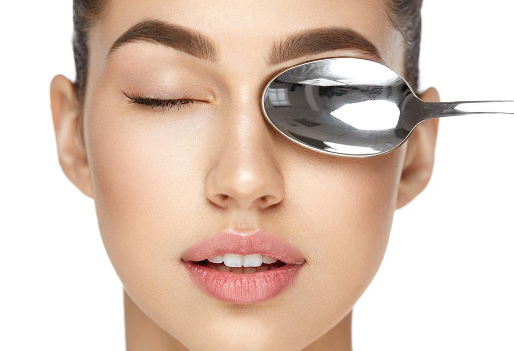 A woman placing a chilled spoon on her eyes