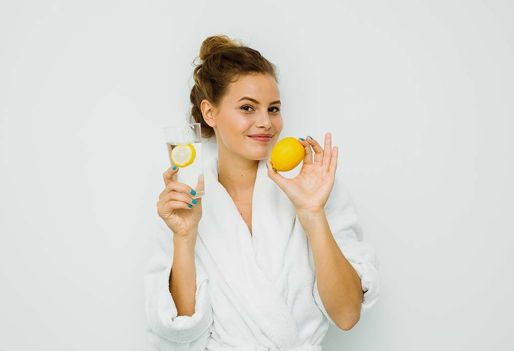 A woman drinking lemon water