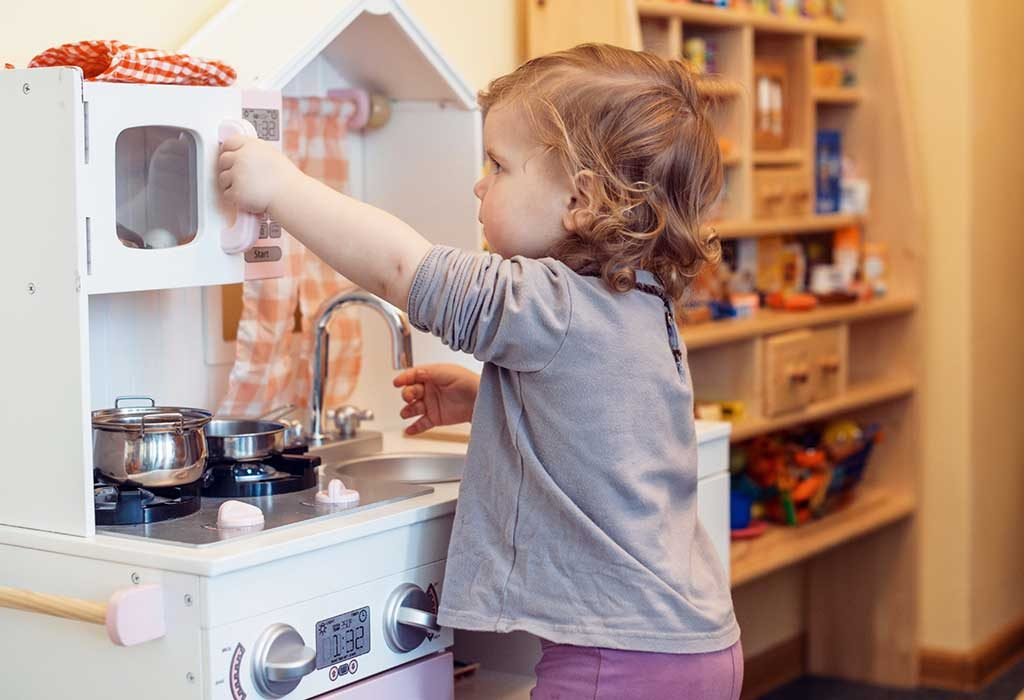 child playing with a toy kitchen