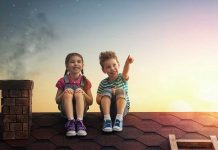 boy and girl watching the sky together on a roof