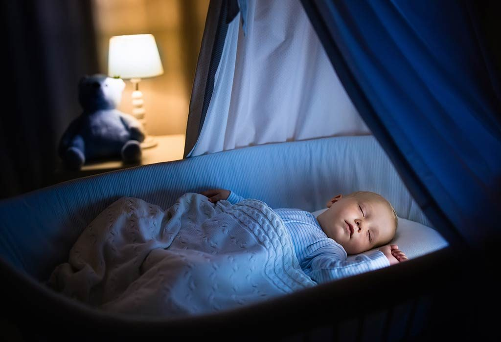 A baby sleeping in a bassinet at night