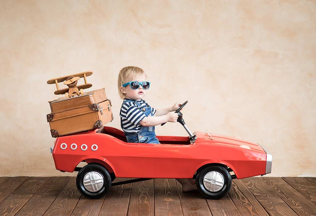 baby driving a toy car with luggage